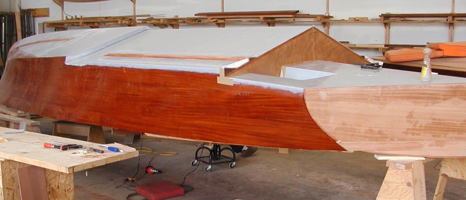Applying fiberglass cloth to hull of Jacqueline before painting