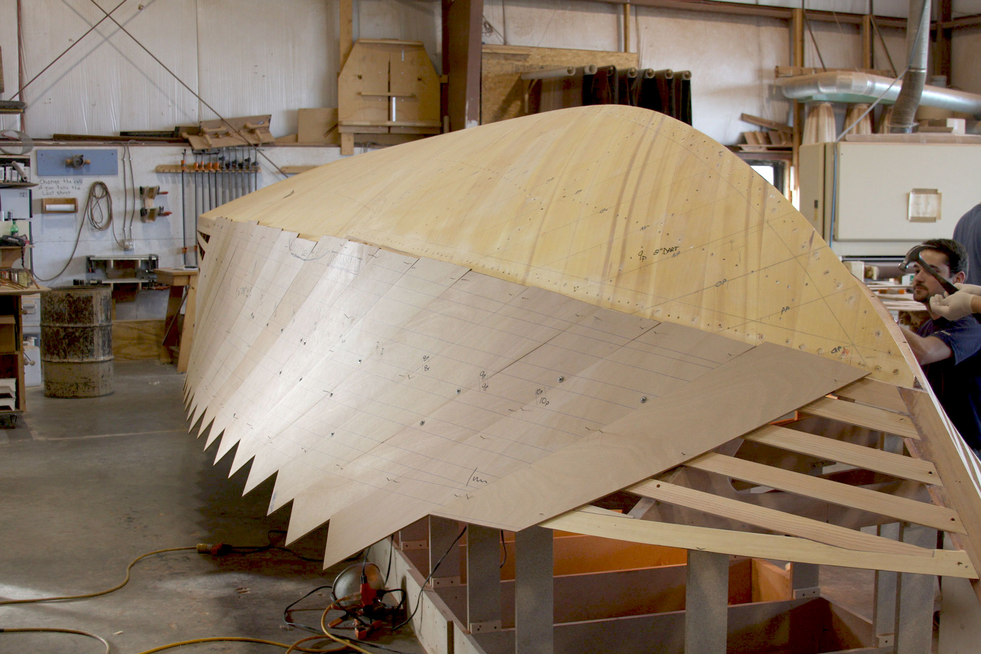 Cold molded planking being secured on hull