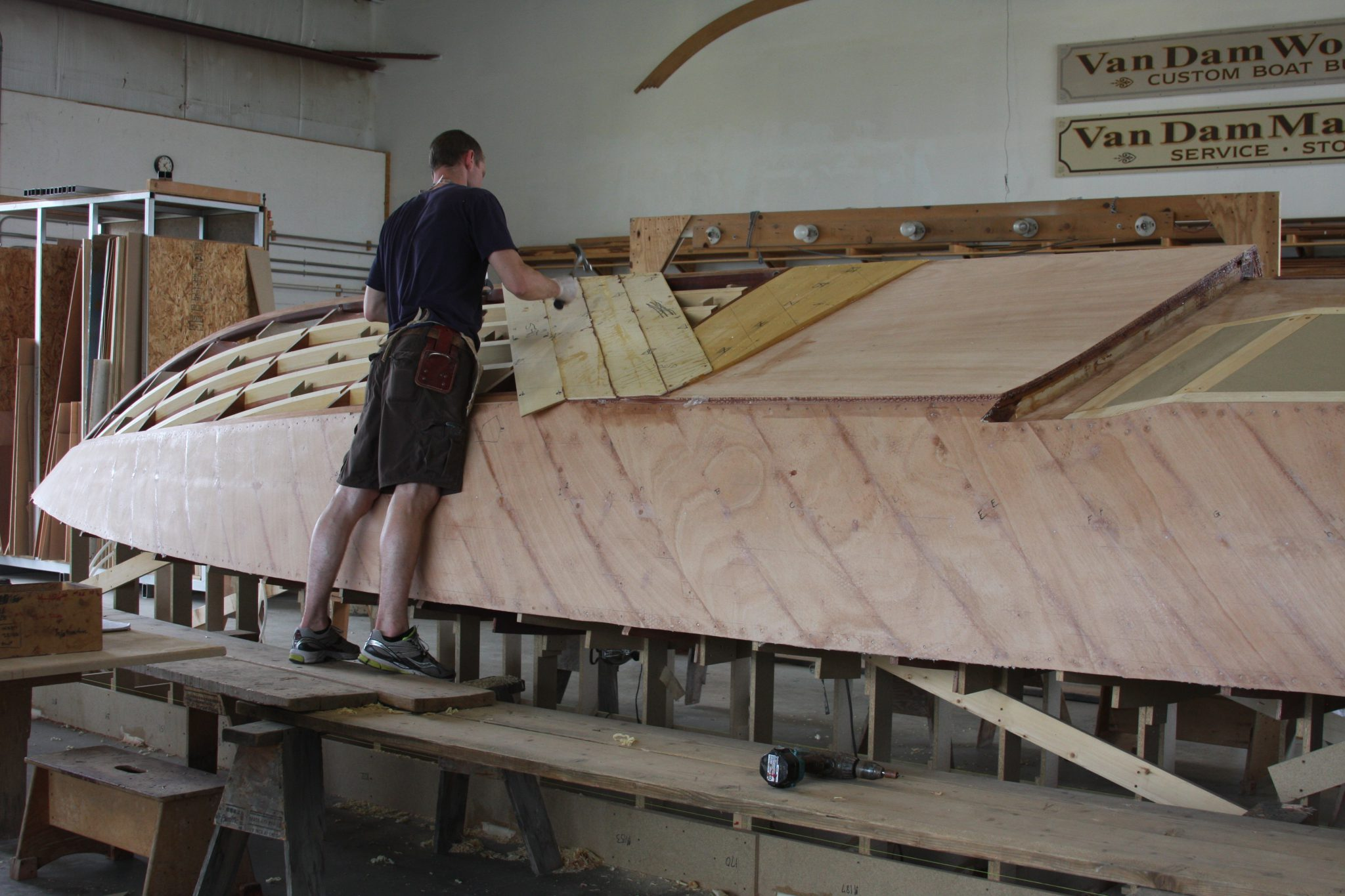 Craftsman adding planking to hull of VZ